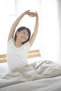 ベッドの上でストレッチをする女性の素材 [FYI01033366]