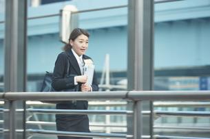 書類を持って急いでいる働く女性の素材 [FYI01033509]