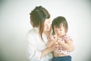 クッキーを食べている赤ちゃんをだっこしているお母さんの素材 [FYI01033514]