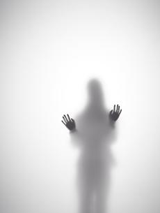 壁に両手をつく女性のシルエットの素材 [FYI01033558]