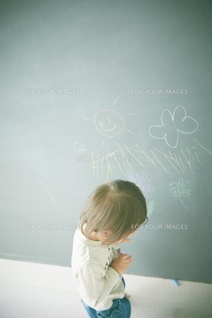 黒板にお絵かきをしている赤ちゃんの素材 [FYI01033566]