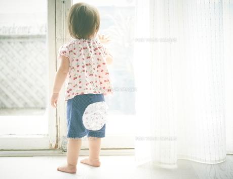 窓の外を見つめている赤ちゃんの素材 [FYI01033574]