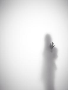 壁に手をつく女性のシルエットの素材 [FYI01033599]