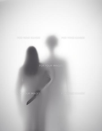 男に襲われそうになっている女性が背後に包丁を持つシルエットの素材 [FYI01033617]