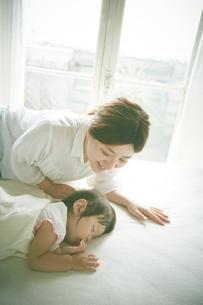 ベッドの上でお昼寝する赤ちゃんをお母さんが優しく見つめているの素材 [FYI01033629]