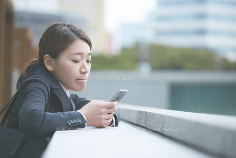 スマホを確認する働く女性の素材 [FYI01033635]