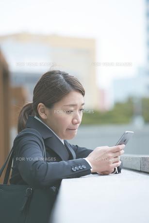 スマホを確認する働く女性の素材 [FYI01033647]
