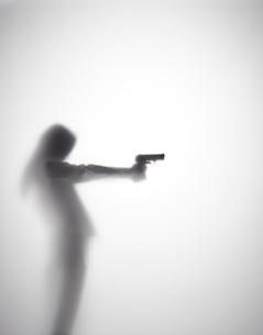 銃を持つ女性のシルエットの素材 [FYI01033654]