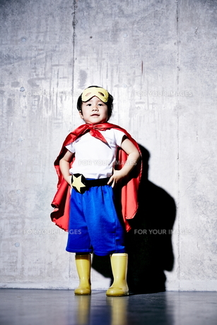 コンクリートの壁の前でポーズをキメるヒーローの男の子の素材 [FYI01033657]
