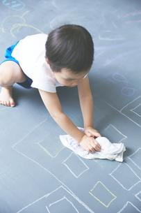 大きな黒板の落書きを消している男の子のアップの素材 [FYI01033662]