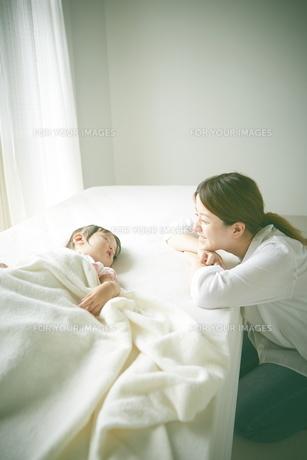 ベッドの上でお昼寝する赤ちゃんをお母さんが優しく見つめているの素材 [FYI01033672]