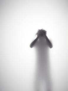 頭を抱えている男性のシルエットの素材 [FYI01033674]