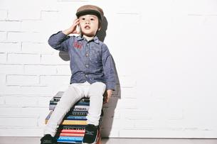 本の椅子に座って電話をするハンチングを被った男の子の素材 [FYI01033681]