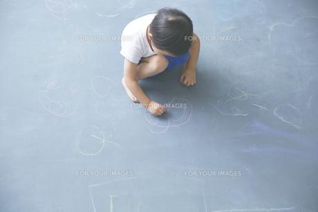 大きな黒板に落書きをして遊ぶ男の子の素材 [FYI01033683]