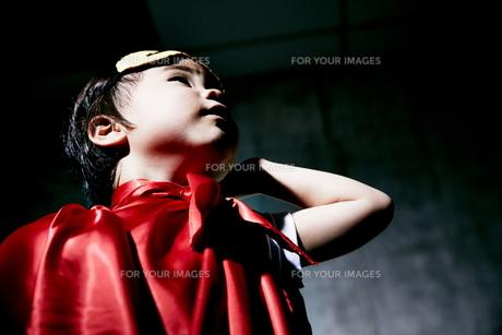 コンクリートの壁の前でポーズをキメるヒーローの男の子のアップの素材 [FYI01033693]