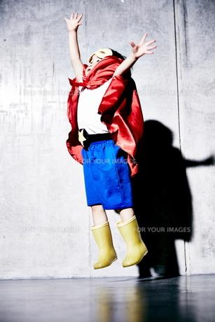 コンクリートの壁の前でジャンプをするヒーローの男の子の素材 [FYI01033724]