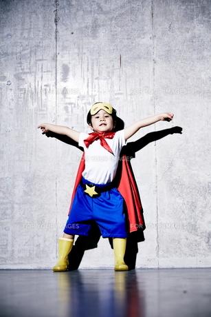 コンクリートの壁の前でポーズをキメるヒーローの男の子の素材 [FYI01033740]