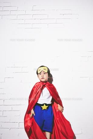 レンガの壁の前で勝利のポーズをするヒーローの男の子の素材 [FYI01033744]