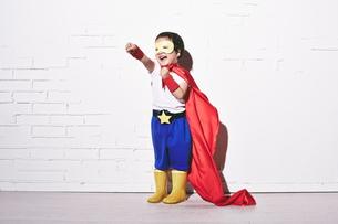 レンガの壁の前でパンチをするヒーローの男の子の素材 [FYI01033749]