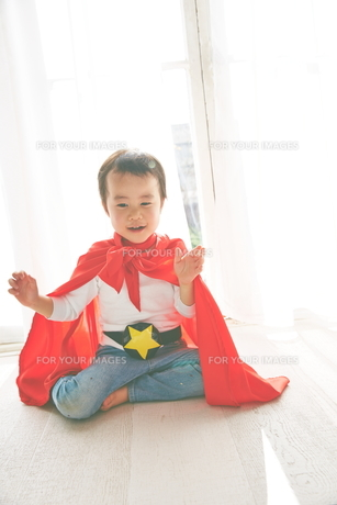 窓辺で楽しそうにしているヒーローの男の子の素材 [FYI01033752]