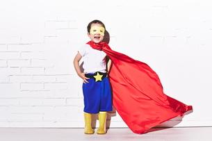 レンガの壁の前で勝利のポーズをするヒーローの男の子の素材 [FYI01033753]