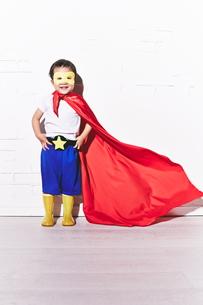 レンガの壁の前で勝利のポーズをするヒーローの男の子の素材 [FYI01033765]