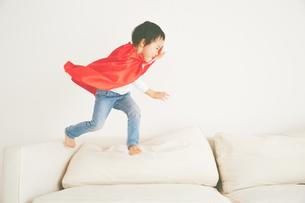 ソファーで元気よく走り回るヒーローの男の子の素材 [FYI01033785]