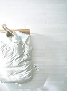 白い床の寝室にあるベットで起床した女性の素材 [FYI01033791]