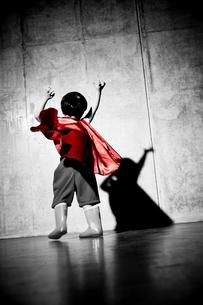 コンクリートの壁の前でポーズをキメるヒーローの男の子の素材 [FYI01033801]