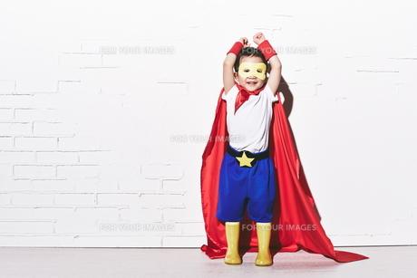 レンガの壁の前で今にも飛び立ちそうなヒーローの男の子の素材 [FYI01033807]