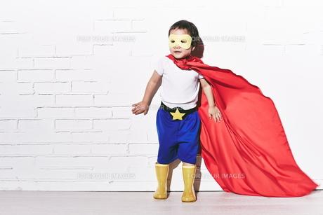 レンガの壁の前で待ち構えているヒーローの男の子の素材 [FYI01033813]