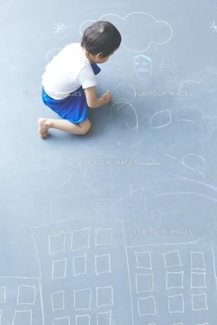 大きな黒板に落書きをして遊ぶ男の子の素材 [FYI01033817]