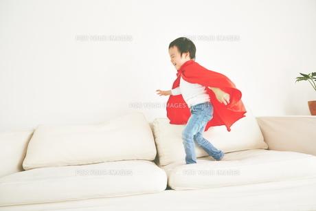 ソファーで元気よく走り回るヒーローの男の子の素材 [FYI01033823]