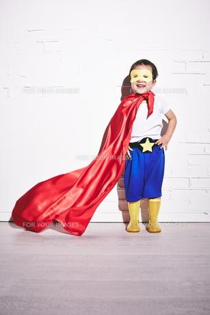 レンガの壁の前で勝利のポーズをするヒーローの男の子の素材 [FYI01033825]