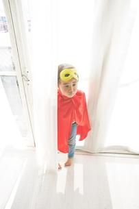 窓辺で悲しそうにしているヒーローの男の子の素材 [FYI01033829]