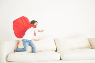 ソファーで元気よく走り回るヒーローの男の子の素材 [FYI01033833]