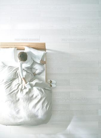 白い床の寝室にあるベットで起床した女性の素材 [FYI01033847]