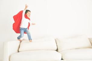 ソファーで元気よく走り回るヒーローの男の子の素材 [FYI01033850]