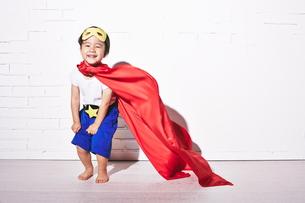 レンガの壁の前で勝利のポーズをするヒーローの男の子の素材 [FYI01033854]