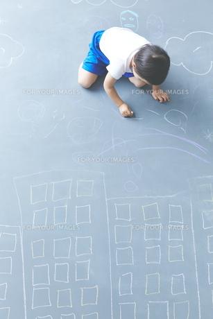 大きな黒板に落書きをして遊ぶ男の子の素材 [FYI01033872]
