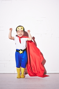 レンガの壁の前で勝利のポーズをするヒーローの男の子の素材 [FYI01033874]