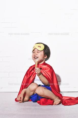 レンガの壁の前でお菓子を食べるヒーローの男の子の素材 [FYI01033875]
