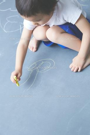 大きな黒板に落書きをして遊ぶ男の子のアップの素材 [FYI01033876]