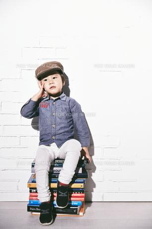 本の椅子に座って電話をするハンチングを被った男の子の素材 [FYI01033888]