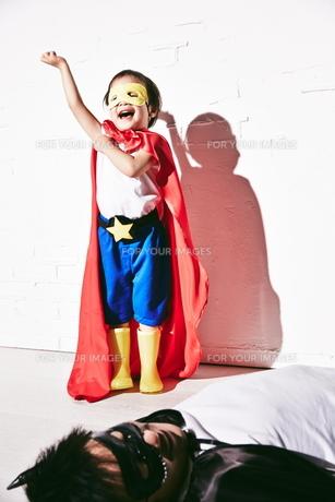 悪者をやっつけて勝利のポーズをするヒーローの男の子の素材 [FYI01033995]