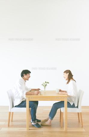 話をする夫婦と白い壁と茶色の木の床の素材 [FYI01034076]
