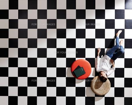 黒と白のタイルに寝ている女性の素材 [FYI01034079]