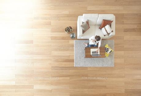 茶色の木の床とコーヒーを飲む女性の素材 [FYI01034081]