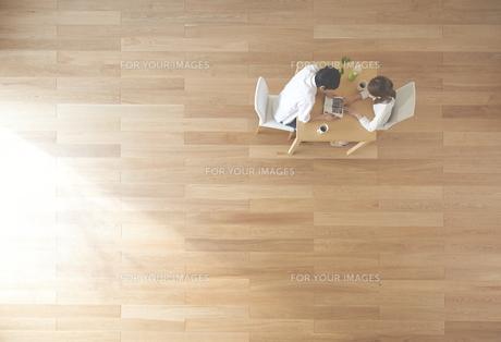 茶色の木の床と本を読む夫婦の素材 [FYI01034093]