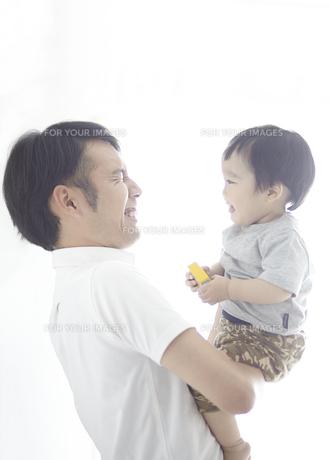 父親に抱かれながら笑い合う子供の素材 [FYI01034165]